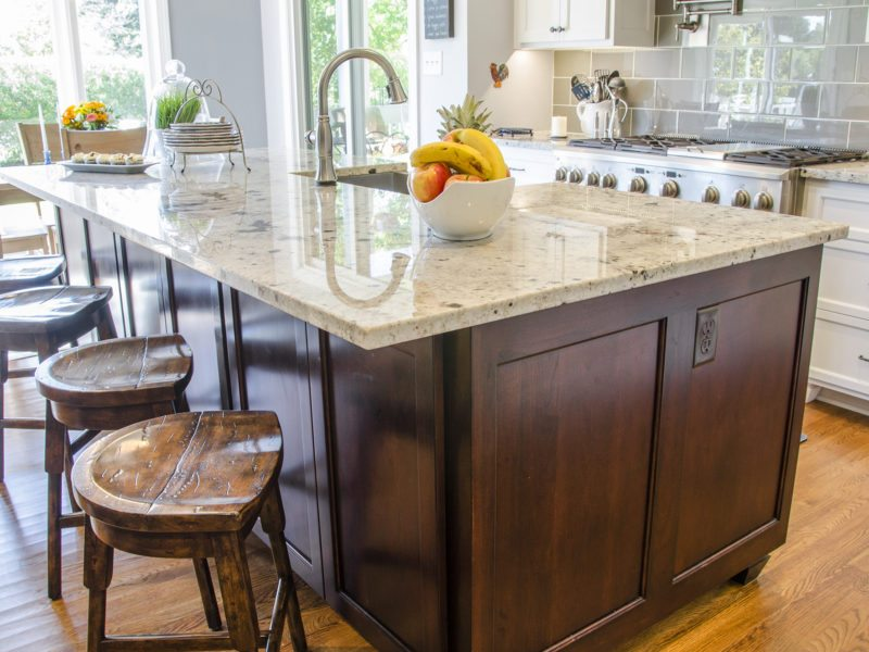 Large kitchen island with dark wood and granite countertops