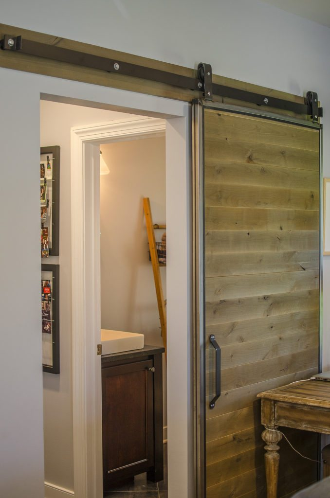 Rustic barn doors separate the family room from the mud room