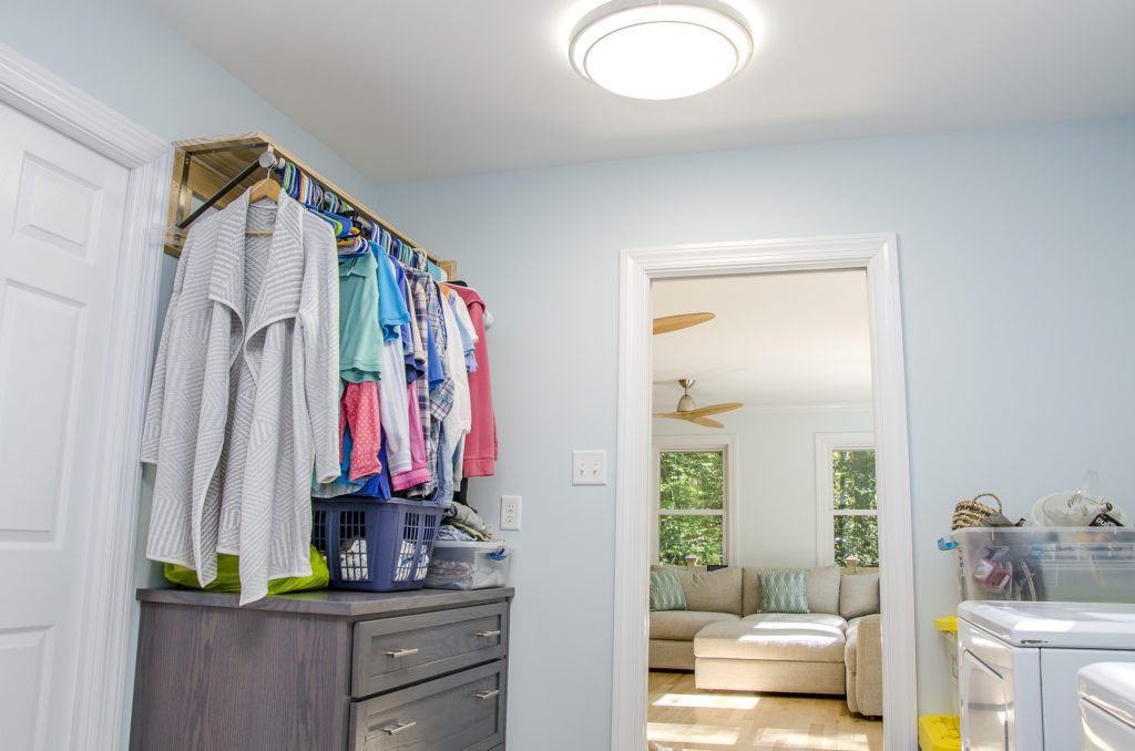 laundry room with a drying rack and custom cabinetry